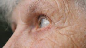 Ögon av den gamla kvinnan som ser upp och flyttar sig därefter från sida för att sid Ögon av en äldre dam med skrynklor runt om d stock video