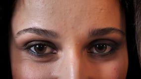 Ögon av den härliga kvinnan med mörkt hår ler som håller ögonen på på kameran, tegelstenbakgrund lager videofilmer