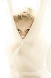 Ögon av den lilla blonda flickan hiden vid gardinen royaltyfri bild