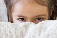 Ögon av den lyckliga ungen som spelar som döljer Fotografering för Bildbyråer