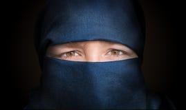 Ögon av den unga kvinnan som skylas med den blåa niqabhalsduken Lågt nyckel- foto royaltyfri fotografi