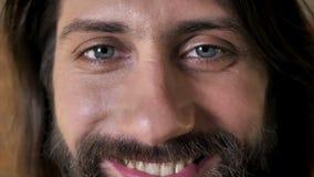 Ögon av den unga söta brunettmannen med skägget håller ögonen på på kameran som ler, tegelstenbakgrund stock video