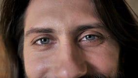 Ögon av den unga trevliga brunettmannen med skägget håller ögonen på på kameran som ler, tegelstenbakgrund lager videofilmer