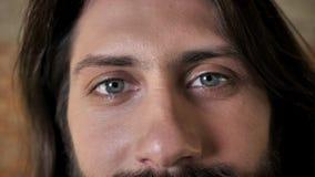 Ögon av den unga trevliga brunettmannen med skägget håller ögonen på på kameran, tegelstenbakgrund lager videofilmer