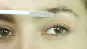 Ögon av en flickanärbild som applicerar genomskinlig medicinsk mascara på ögonfrans, skönhetsalong lager videofilmer