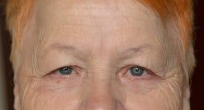 Ögon av en gammal kvinna med skrynklor Närbild arkivbilder