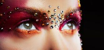 Ögon av en härlig ung kvinna i en ljus märkes- makeup med bergkristaller Royaltyfri Foto