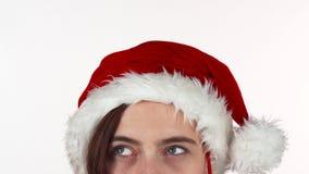 Ögon av en kvinna i julhatt som ler till kameran som isoleras stock video