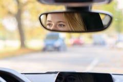 Ögon av en kvinnlig chaufför i spegeln för bakre sikt royaltyfri foto