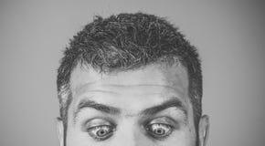 Ögon av mannen med den förvånade framsidan på blå bakgrund Arkivfoto