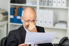 Ögon för affärsmanHolding Document While gnuggbild royaltyfri foto