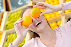 Ögon för hållande apelsiner för dam främsta arkivbild