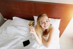 Ögon för slut för kreditkort för kvinnahålldebitering lyckliga i vit säng hemma med solsken royaltyfria bilder