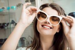 Ögon förtjänar bästa linser och exponeringsglas Stående av den snygga kvinnan i optikerlagret som väljer nya par av stilfullt royaltyfria bilder