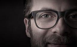 Ögon och exponeringsglas - slut för framsida för man` s upp makro Arkivfoto