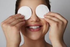 Ögon och framsida för hud för härlig flickamodell uppfriskande med vita bomullsblock över grå studiobakgrund Modell med ljus royaltyfri foto