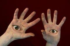Ögon på gigantiska händer royaltyfria foton