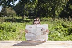 Ögon sticker fram en tidning Arkivfoton