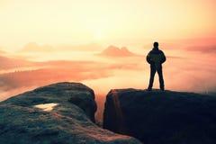 Ögonblick av ensamhet Man på vaggaväldearna och klocka över den dimmiga och dimmiga morgondalen till solen Royaltyfria Bilder