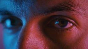 Ögonblickar på han i multicolor neon light En ung mans porträtt på natten under festen i nyljus arkivfilmer