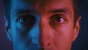 Ögonblickar på han i multicolor neon light En ung mans porträtt på natten under festen i nyljus stock video