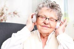 Ögonblicket av avkoppling, vilar farmodern som lyssnar till musik arkivbilder