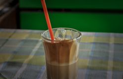 Ögonblicklig coffe i ett exponeringsglas med ett rött sugrör royaltyfri bild