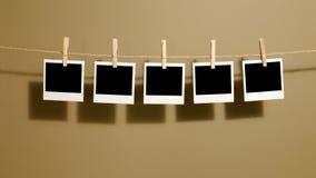 Ögonblickliga fototryck för polaroid- stil som hänger på ett rep eller en tvättande linje, mörka skuggor Arkivbild