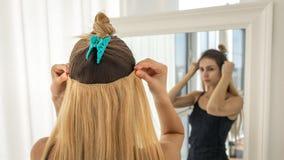 Ögonblickliga hårförlängningar på hårnålar för volym och förlängning blonda trådar arkivbild