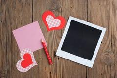 Ögonblickligt foto med den tomma anmärkningen, blyertspennan och hjärtor Royaltyfri Fotografi