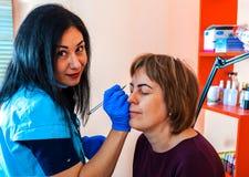 Ögonbrynkorrigering i skönhetsalongen arkivfoton