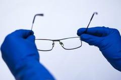 Ögondoktorn väljer upp linserna till patienten Astigmatiska exponeringsglas för låg vision på vit bakgrund i medicinska handskar royaltyfri bild