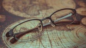 Ögonexponeringsglas på världskarta royaltyfri bild