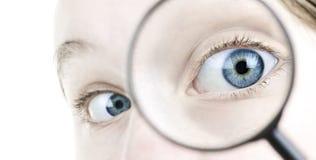 ögonexponeringsglas som ser grundlig förstoring arkivfoto