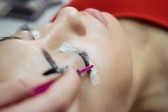 Ögonfransförlängningstillvägagångssätt Kvinnan synar med långa ögonfranser royaltyfri foto