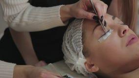 Ögonfransförlängningstillvägagångssätt Kvinnan synar med långa ögonfranser lager videofilmer