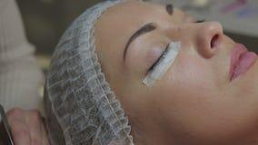 Ögonfransförlängningstillvägagångssätt Kvinnan synar med långa ögonfranser stock video
