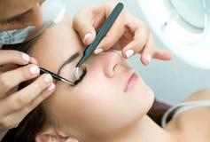 Ögonfransförlängningstillvägagångssätt Kvinnan synar med långa ögonfranser Arkivfoton