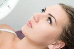Ögonfransförlängningstillvägagångssätt Kvinnan synar med långa ögonfranser Fotografering för Bildbyråer