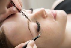 Ögonfransförlängningstillvägagångssätt Kvinnan synar med långa ögonfranser Arkivfoto