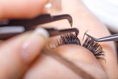Ögonfransförlängningstillvägagångssätt Kvinnan synar med långa ögonfranser Snärtar slut upp, makro, selektiv fokus royaltyfri bild