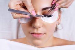 Ögonfransförlängningstillvägagångssätt Kvinnan synar med långa ögonfranser Snärtar slut upp, makro, selektiv fokus arkivbild