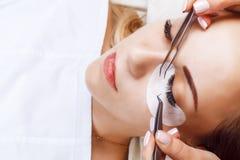 Ögonfransförlängningstillvägagångssätt Kvinnan synar med långa ögonfranser Snärtar slut upp, makro, selektiv fokus arkivfoton