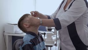 Ögonläkaredroppande tappar in i ögonen av den lilla patienten arkivfilmer