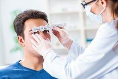 Ögonläkaren kontrollerar upp patient i sjukhus för ögondoktor royaltyfri bild