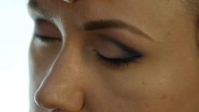 Ögonmakeupkvinna som applicerar ögonskuggapulver Stylisten gör sminket för kvinnlig vid eyeliner lager videofilmer