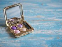 Ögonskugga i en guld- ask med spegeln på den blåa trätabellen Royaltyfri Foto