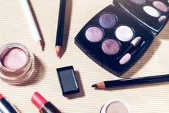 Ögonskuggapalett, krönpulver, abc-bok, ögonblyertspennor och läppstift Fotografering för Bildbyråer