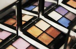 Ögonskuggor på shoppar fönstret, färgkombinationer, gammafashionable purpurfärgade blommor, selektiv fokus royaltyfria foton