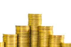 Ökande kolonner av mynt, högar av guld- mynt som är ordnade som ett G Arkivfoton